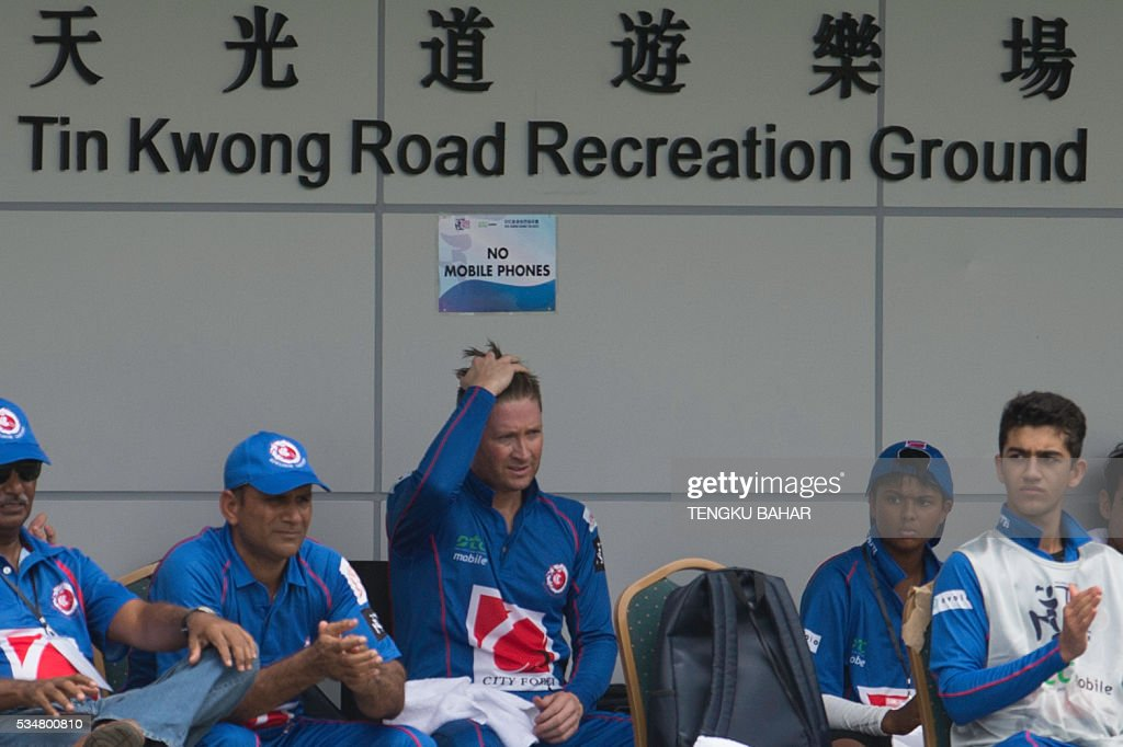 Michael Clarke of the Kowloon Cantons (C) reacts as he looks on with teammates after he was dismissed for six runs while playing against Hung Hom JD Jaguars during the Hong Kong T20 Blitz cricket tournament in Hong Kong on May 28, 2016. Former Australia captain Michael Clarke on May 27 said his body felt 15 years younger after a spell away from cricket as he prepared for a comeback at the Hong Kong T20 Blitz. / AFP / TENGKU