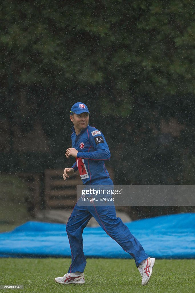 Michael Clarke of the Kowloon Cantons runs to the pavilion as rain stops play during the Hong Kong T20 Blitz cricket tournament in Hong Kong on May 28, 2016. Former Australia captain Michael Clarke on May 27 said his body felt 15 years younger after a spell away from cricket as he prepared for a comeback at the Hong Kong T20 Blitz. / AFP / TENGKU