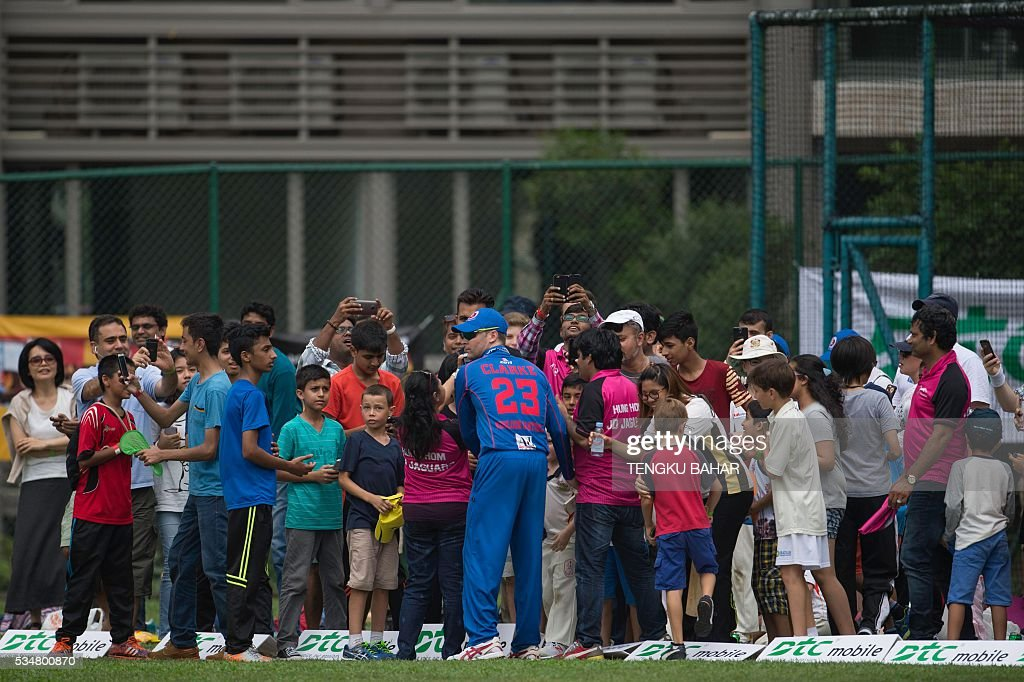 Michael Clarke of the Kowloon Cantons signs autographs for fans in between play against Hung Hom JD Jaguars during the Hong Kong T20 Blitz cricket tournament in Hong Kong on May 28, 2016. Former Australia captain Michael Clarke on May 27 said his body felt 15 years younger after a spell away from cricket as he prepared for a comeback at the Hong Kong T20 Blitz. / AFP / TENGKU
