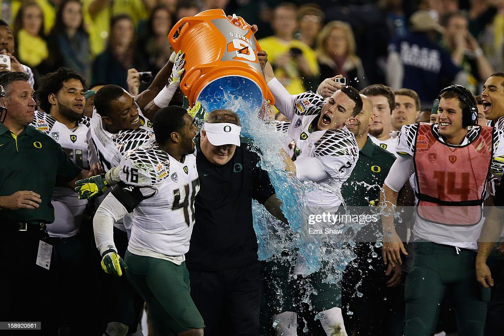 Michael Clay #46 and Bryan Bennett #2 dump the gatorade cooler on head coach <a gi-track='captionPersonalityLinkClicked' href=/galleries/search?phrase=Chip+Kelly&family=editorial&specificpeople=6161242 ng-click='$event.stopPropagation()'>Chip Kelly</a> of the Oregon Ducks after their 35 to 17 victory over the Kansas State Wildcats in the Tostitos Fiesta Bowl at University of Phoenix Stadium on January 3, 2013 in Glendale, Arizona.