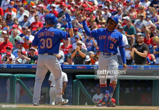 Michael Conforto of the New York Mets high fives Curtis Granderson at home plate after hitting a tworun home run in the first inning during a game...