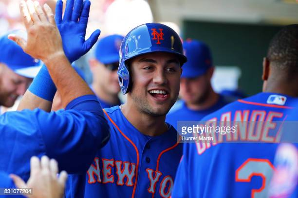 Michael Conforto of the New York Mets high fives teammates in the dugout after hitting a tworun home run in the first inning during a game against...