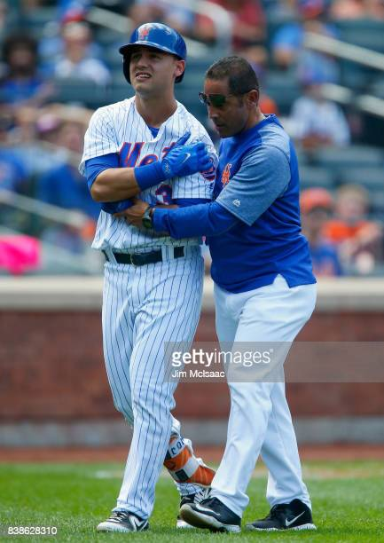 Michael Conforto of the New York Mets leaves a game against the Arizona Diamondbacks with trainer Ray Ramirez after an injury during an atbat in the...