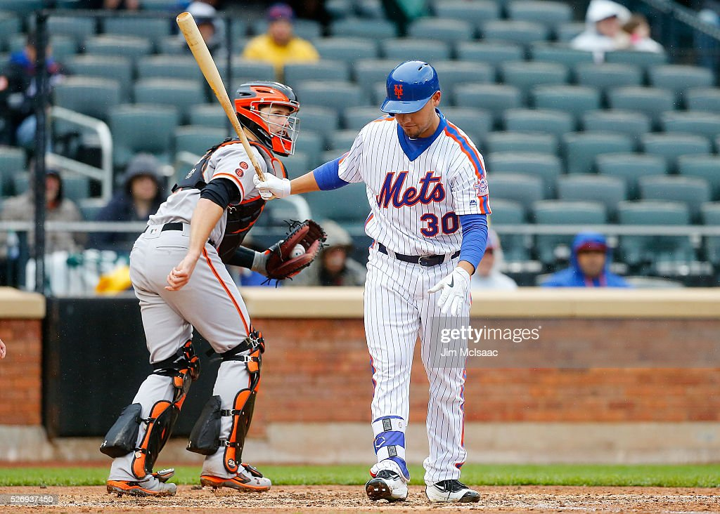 Michael Conforto #30 of the New York Mets reacts after striking out to end the fifth inning as Buster Posey #28 of the San Francisco Giants heads back to the dugout at Citi Field on May 1, 2016 in the Flushing neighborhood of the Queens borough of New York City.