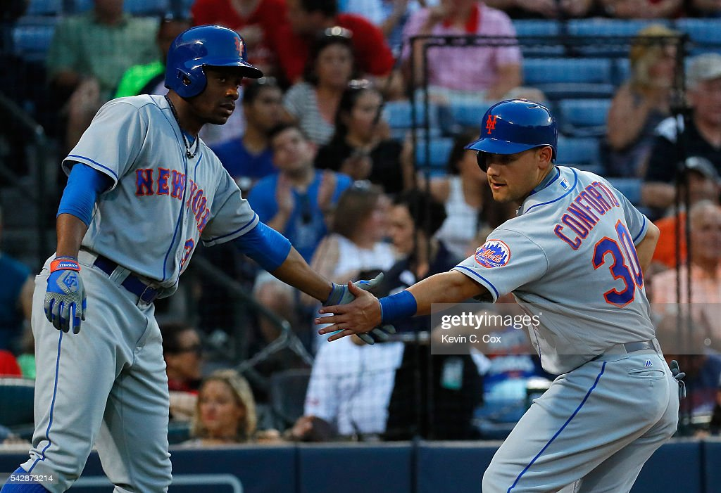 Michael Conforto #30 of the New York Mets reacts with Curtis Granderson #3 after scoring on a sacrifice fly hit by Steven Matz #32 in the fourth inning against the Atlanta Braves at Turner Field on June 24, 2016 in Atlanta, Georgia.