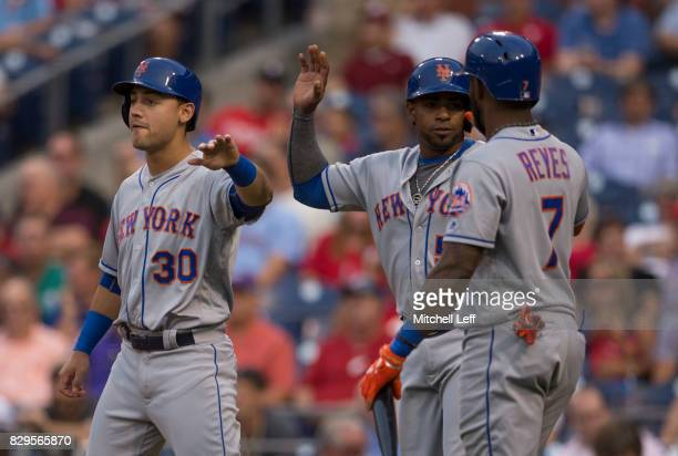 Michael Conforto Yoenis Cespedes and Jose Reyes of the New York Mets celebrate after a three run home run hit by Wilmer Flores of the New York Mets...