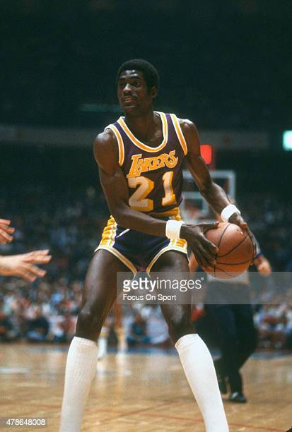 Michael Cooper of the Los Angeles Lakers looks to pass against the Philadelphia 76ers during an NBA basketball game circa 1980 at The Spectrum in...