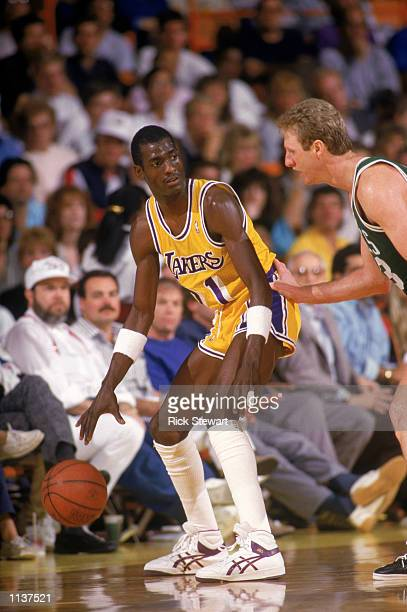 Michael Cooper of the Los Angeles Lakers looks to pass over Larry Bird of the Boston Celtics during an NBA game at the Great Western Forum in Los...