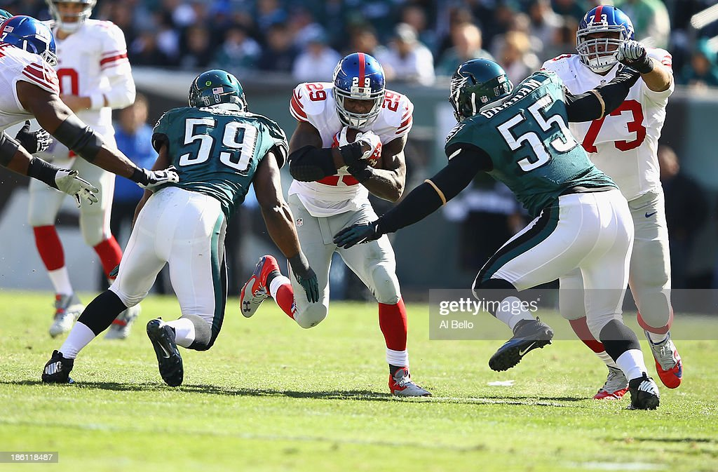Michael Cox #29 of the New York Giants runs into <a gi-track='captionPersonalityLinkClicked' href=/galleries/search?phrase=DeMeco+Ryans&family=editorial&specificpeople=614722 ng-click='$event.stopPropagation()'>DeMeco Ryans</a> #59 of the Philadelphia Eagles and <a gi-track='captionPersonalityLinkClicked' href=/galleries/search?phrase=Brandon+Graham&family=editorial&specificpeople=4500988 ng-click='$event.stopPropagation()'>Brandon Graham</a> #55 of the Philadelphia Eagles during their game at Lincoln Financial Field on October 27, 2013 in Philadelphia, Pennsylvania.