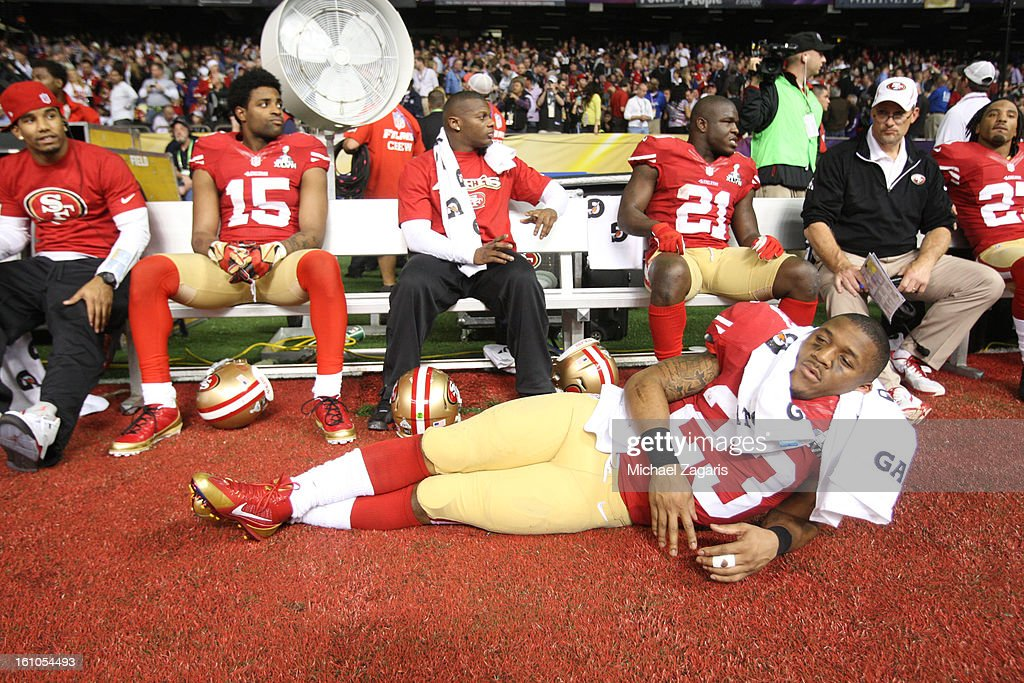 Michael Crabtree #15, LaMichael James #23, Kendall Hunter #32 and Frank Gore #21 of the San Francisco 49ers relax on the bench as they wait for the power to come back on during Super Bowl XLVII against the Baltimore Ravens at the Mercedes-Benz Superdome on February 3, 2013 in New Orleans, Louisiana. The Ravens won 34-31.