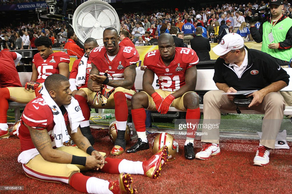 Michael Crabtree #15, LaMichael James #23, Kendall Hunter #32, Vernon Davis #85, Frank Gore #21 and Running Backs Coach Tom Rathman of the San Francisco 49ers relax on the bench as they wait for the power to come back on during Super Bowl XLVII against the Baltimore Ravens at the Mercedes-Benz Superdome on February 3, 2013 in New Orleans, Louisiana. The Ravens won 34-31.