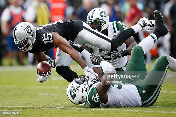 Michael Crabtree of the Oakland Raiders breaks a tackle from Demario Davis of the New York Jets as he runs for a 36yard touchdown reception against...