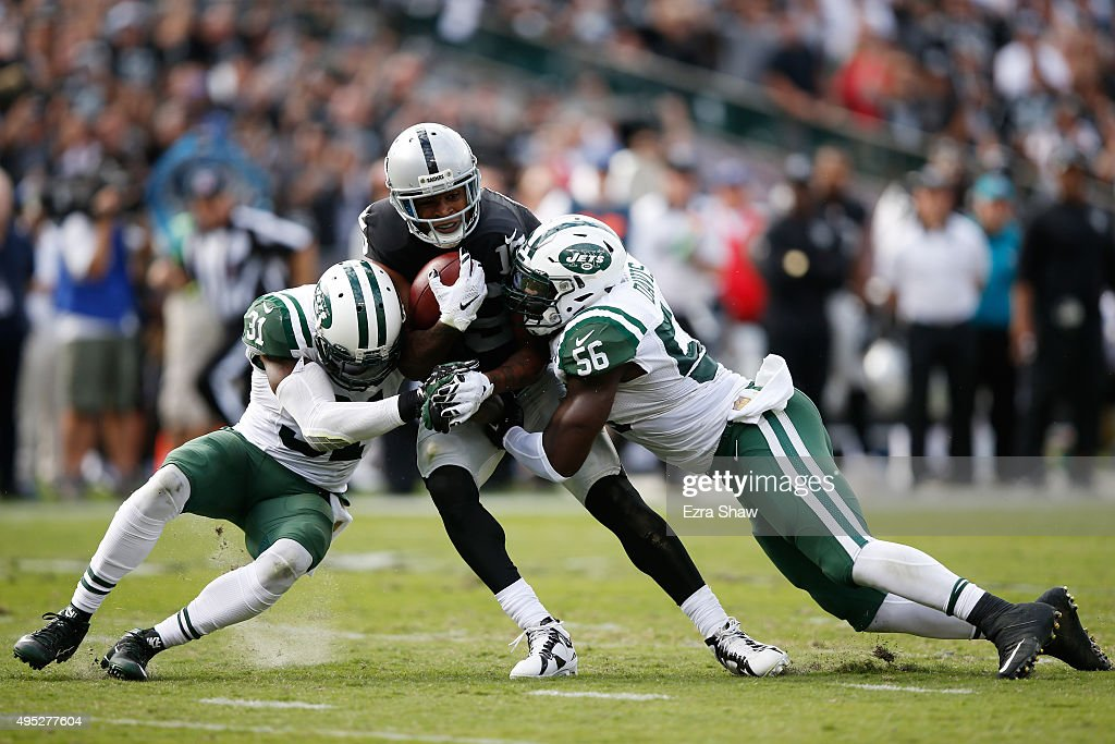 Michael Crabtree of the Oakland Raiders breaks a tackle from Demario Davis and Antonio Cromartie of the New York Jets as he runs for a 36yard...