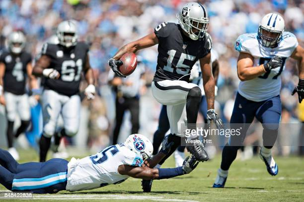 Michael Crabtree of the Oakland Raiders breaks the tackle of Jayon Brown of the Tennessee Titans at Nissan Stadium on September 10 2017 in Nashville...