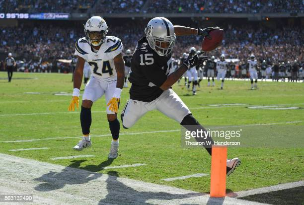 Michael Crabtree of the Oakland Raiders fights off the tackle of Trevor Williams of the Los Angeles Chargers to score a touchdown during an NFL...