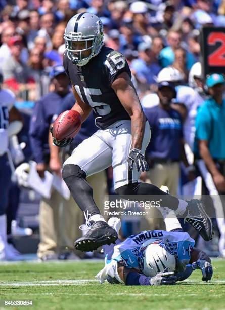 Michael Crabtree of the Oakland Raiders jumps over Jayon Brown of the Tennessee Titans during the first half at Nissan Stadium on September 10 2017...