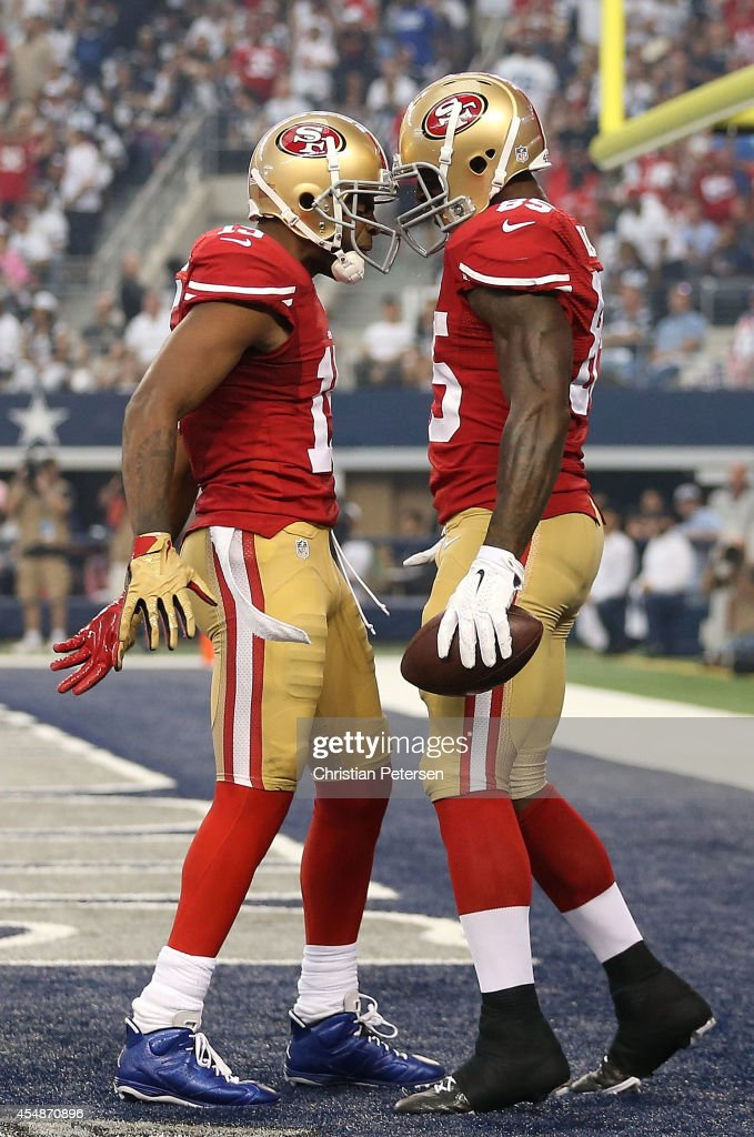 Michael Crabtree #15 of the San Francisco 49ers and Vernon Davis #85 of the San Francisco 49ers celebrate Davis' touchdown against the Dallas Cowboys in the first half at AT&T Stadium on September 7, 2014 in Arlington, Texas.