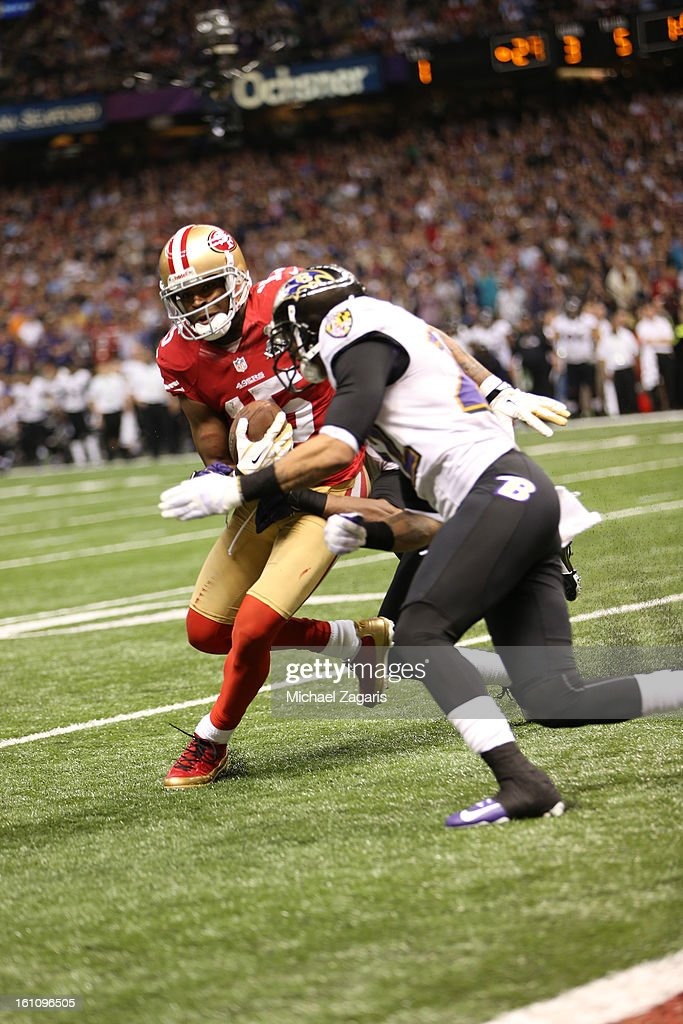 Michael Crabtree #15 of the San Francisco 49ers loses the ball on a big hit by the Baltimore Ravens during Super Bowl XLVII at the Mercedes-Benz Superdome on February 3, 2013 in New Orleans, Louisiana. The Ravens won 34-31.