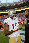 Michael Crabtree of the San Francisco 49ers talks with DJ Bolden on the field prior to the game against the Denver Broncos at Sports Authority Field...