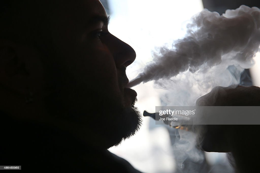 Michael Crespo, a salesman, waits for customers as he enjoys an electronic cigarette at the Vapor Shark store on April 24, 2014 in Miami, Florida. Brandon Leidel, CEO, Director of Operations Vapor Shark, said he welcomes the annoucement by the Food and Drug Administration that they are proposing the first federal regulations on electronic cigarettes, which would ban sales of the popular devices to anyone under 18 and require makers to gain FDA approval for their products.