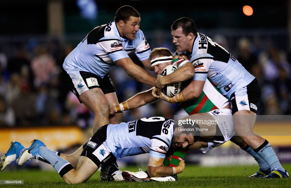 Michael Crocker of the Rabbitohs is tackled by the Sharks defence during the round 24 NRL match between the Cronulla Sharks and the South Sydney...