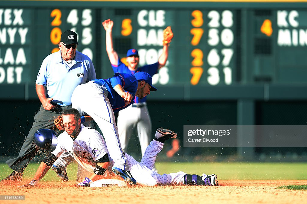 <a gi-track='captionPersonalityLinkClicked' href=/galleries/search?phrase=Michael+Cuddyer&family=editorial&specificpeople=208127 ng-click='$event.stopPropagation()'>Michael Cuddyer</a> #3 of the Colorado Rockies is tagged out by <a gi-track='captionPersonalityLinkClicked' href=/galleries/search?phrase=Omar+Quintanilla&family=editorial&specificpeople=551479 ng-click='$event.stopPropagation()'>Omar Quintanilla</a> #3 of the New York Mets in the eighth inning of the game at Coors Field on June 27, 2013 in Denver, Colorado.Cuddyer got a hit for a team-record 24th straight game.