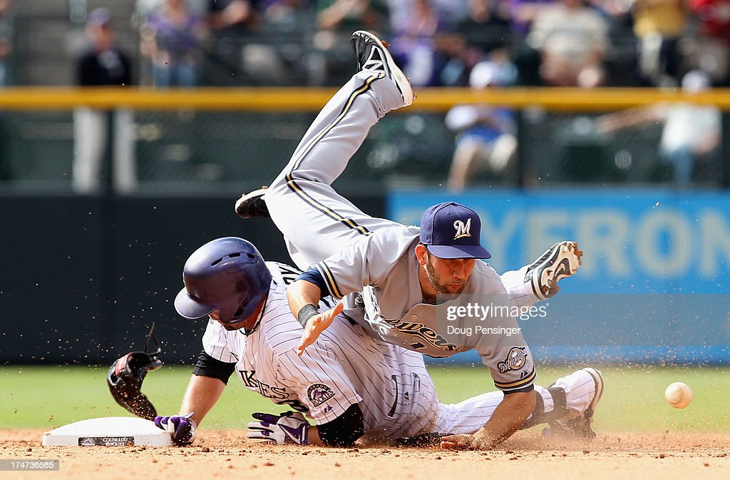 <a gi-track='captionPersonalityLinkClicked' href=/galleries/search?phrase=Michael+Cuddyer&family=editorial&specificpeople=208127 ng-click='$event.stopPropagation()'>Michael Cuddyer</a> #3 of the Colorado Rockies slides safely into second base with an RBI double as a shortstop Jeff Bianchi #14 of the Milwaukee Brewers tries to collect the throw after colliding with Cuddyer and loosing his glove in the eighth inning at Coors Field on July 28, 2013 in Denver, Colorado. The Rockies defeated the Brewers 6-5.