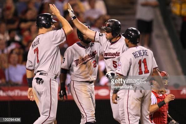 Michael Cuddyer of the Minnesota Twins celebrates wtih Joe Mauer Denard Span and Ben Revere after they all score on Cuddyer's grand slam home run in...