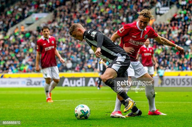 Michael Cuisance of Borussia Moenchengladbach and Felix Klaus of Hannover 96 battle for the ball during the Bundesliga match between Borussia...