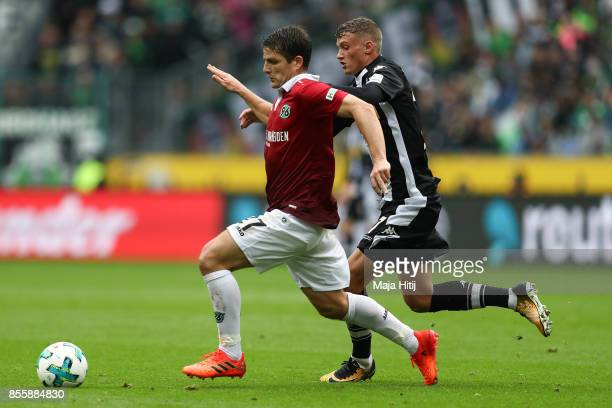 Michael Cuisance of Moenchengladbach and Pirmin Schwegler of Hannover battle for the ball during the Bundesliga match between Borussia...