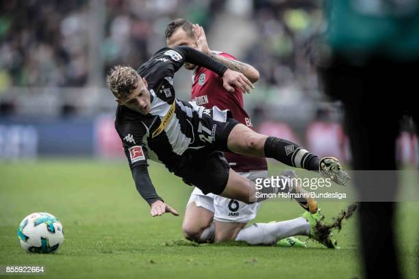 Michael Cuisance of Moenchengladbach is tackled by Marvin Bakalorz of Hannover during the Bundesliga match between Borussia Moenchengladbach and...