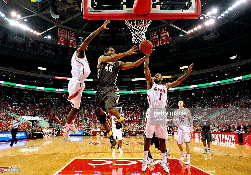 Michael Davenport #45 of the St. Bonaventure Bonnies drives between C.J. Leslie #5 and Richard Howell #1 of the North Carolina State Wolfpack during play at PNC Arena on December 22, 2012 in Raleigh, North Carolina. North Carolina State won 92-73.