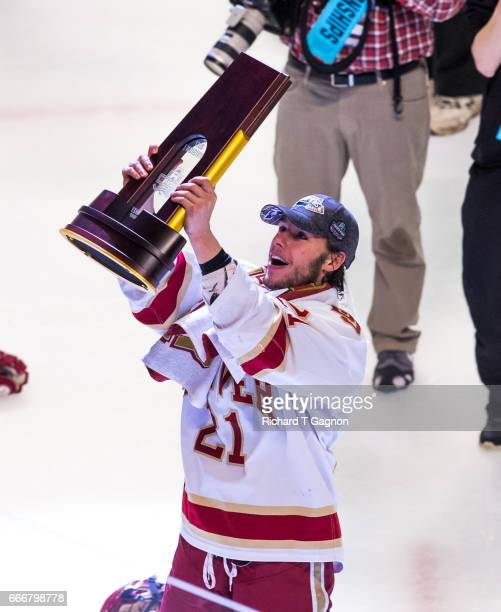 Michael Davies of the Denver Pioneers celebrates a victory against the Minnesota Duluth Bulldogs by raising the championship trophy after the 2017...