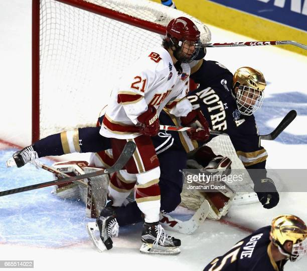 Michael Davies of the Denver Pioneers knocks down Anders Bjork of the Notre Dame Fighting Irish and is called for interference during game two of the...