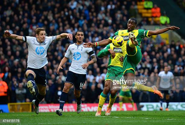 Michael Dawson of Tottenham Hotspur looks on as Sebastien Bassong of Norwich City misses a chance at goal during the Barclays Premier League match...