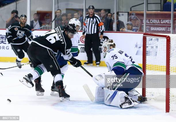 Michael Del Zotto and Jonny Brodzinski of the Los Angeles Kings look on as Jacob Markstrom of the Vancouver Canucks makes a save during their...