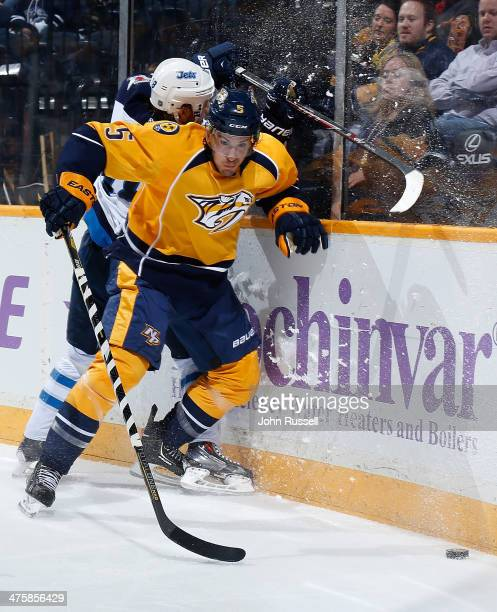 Michael Del Zotto of the Nashville Predators checks Bryan Little of the Winnipeg Jets at Bridgestone Arena on March 1 2014 in Nashville Tennessee