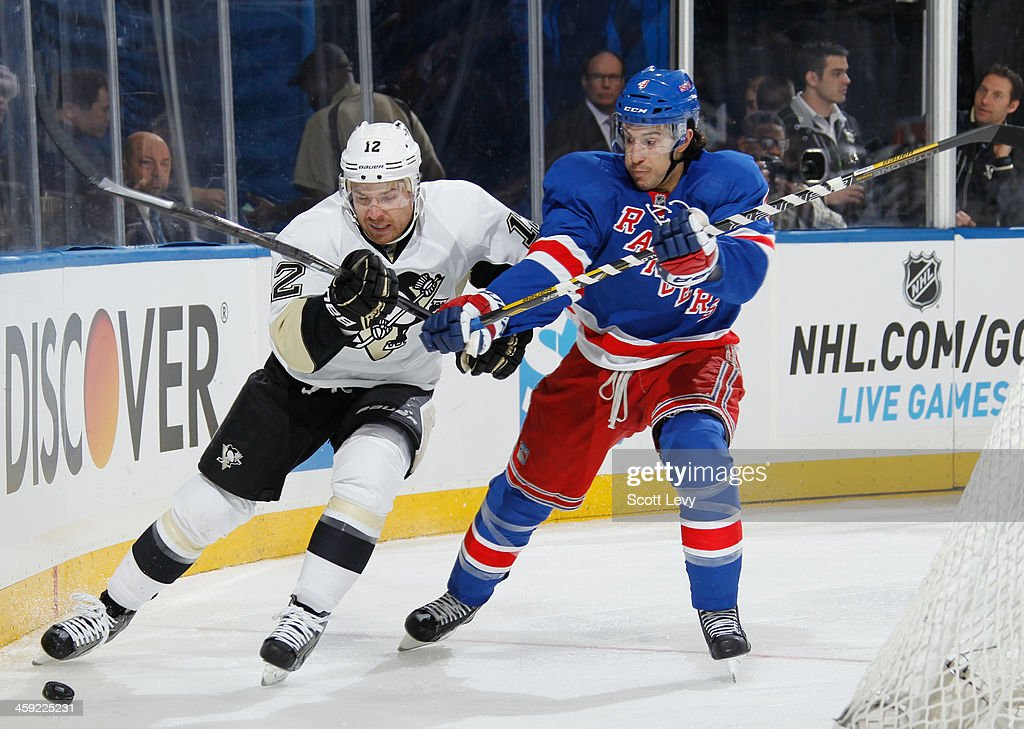 Michael Del Zotto of the New York Rangers and Chuck Kobasew of the Pittsburgh Penguins battle for the puck at Madison Square Garden on December 18...