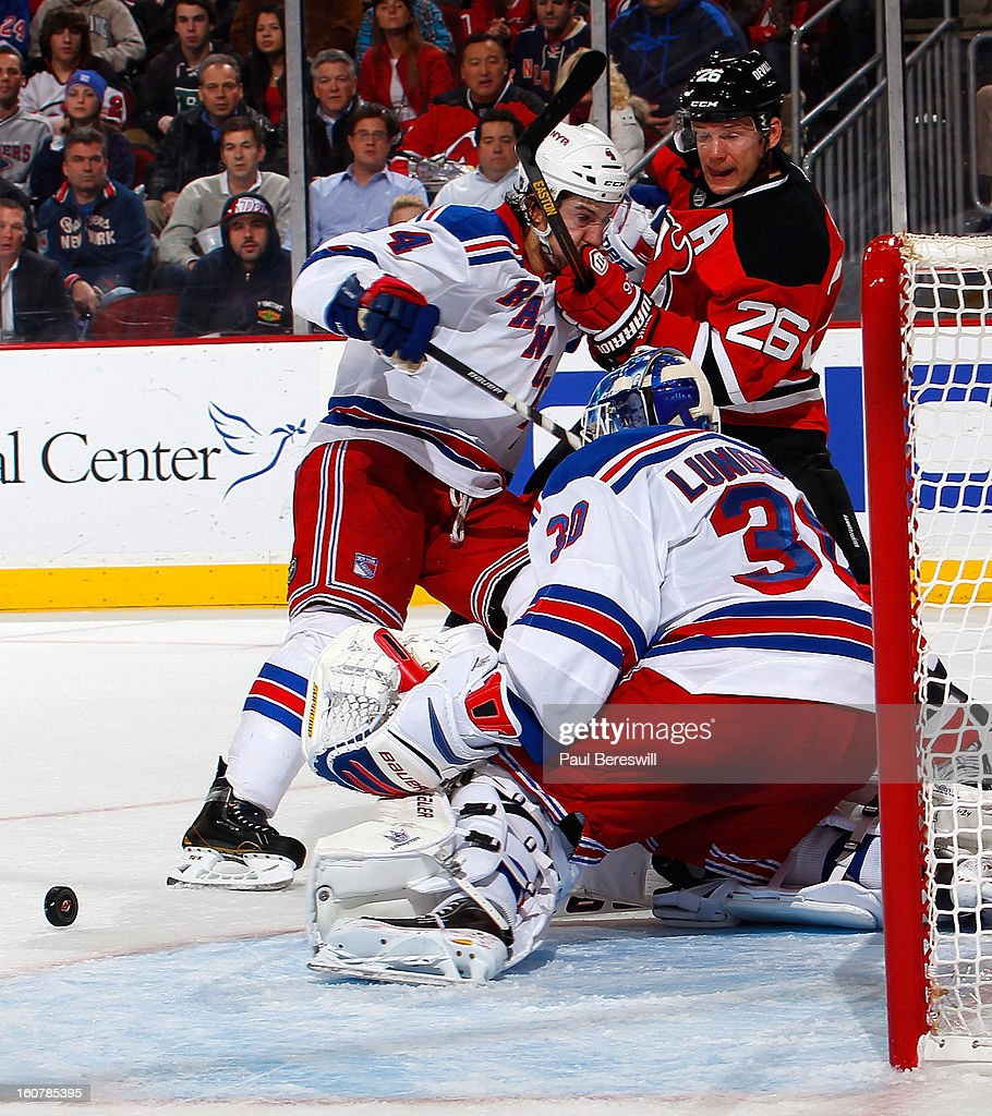Michael Del Zotto #4 of the New York Rangers keeps Patrik Elias #26 of the New Jersey Devils from getting the rebound as goalie Henrik Lundqvist #30 of the Rangers made the save during the third period of an NHL hockey game at Prudential Center on February 5, 2013 in Newark, New Jersey.