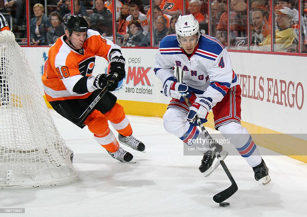 Michael Del Zotto #4 of the New York Rangers maintains control of the puck behind the net while being pursued by Adam Hall #18 of the Philadelphia Flyers on April 16, 2013 at the Wells Fargo Center in Philadelphia, Pennsylvania.