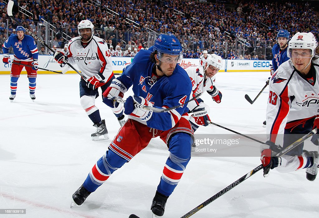 Michael Del Zotto #4 of the New York Rangers skates for the puck in the corner against Jay Beagle #83 of the Washington Capitals in Game Three of the Eastern Conference Quarterfinals during the 2013 NHL Stanley Cup Playoffs at Madison Square Garden on May 6, 2013 in New York City.