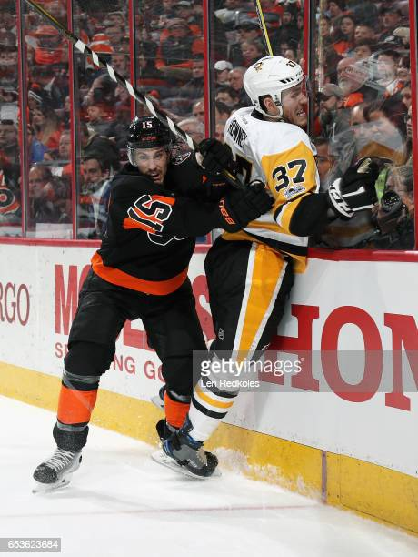 Michael Del Zotto of the Philadelphia Flyers checks Carter Rowney of the Pittsburgh Penguins into the boards on March 15 2017 at the Wells Fargo...
