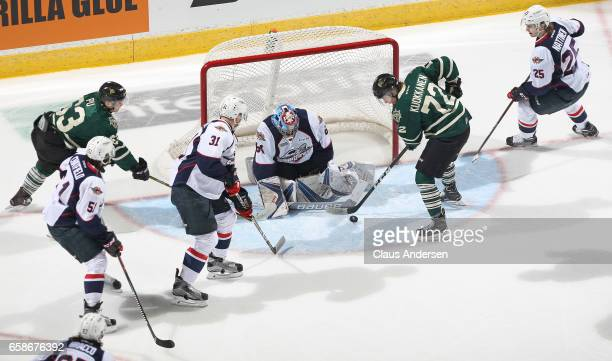 Michael DiPietro of the Windsor Spitfires stops Janne Kuokkanen of the London Knights during Game Two of the OHL Western Conference Quarter Finals at...