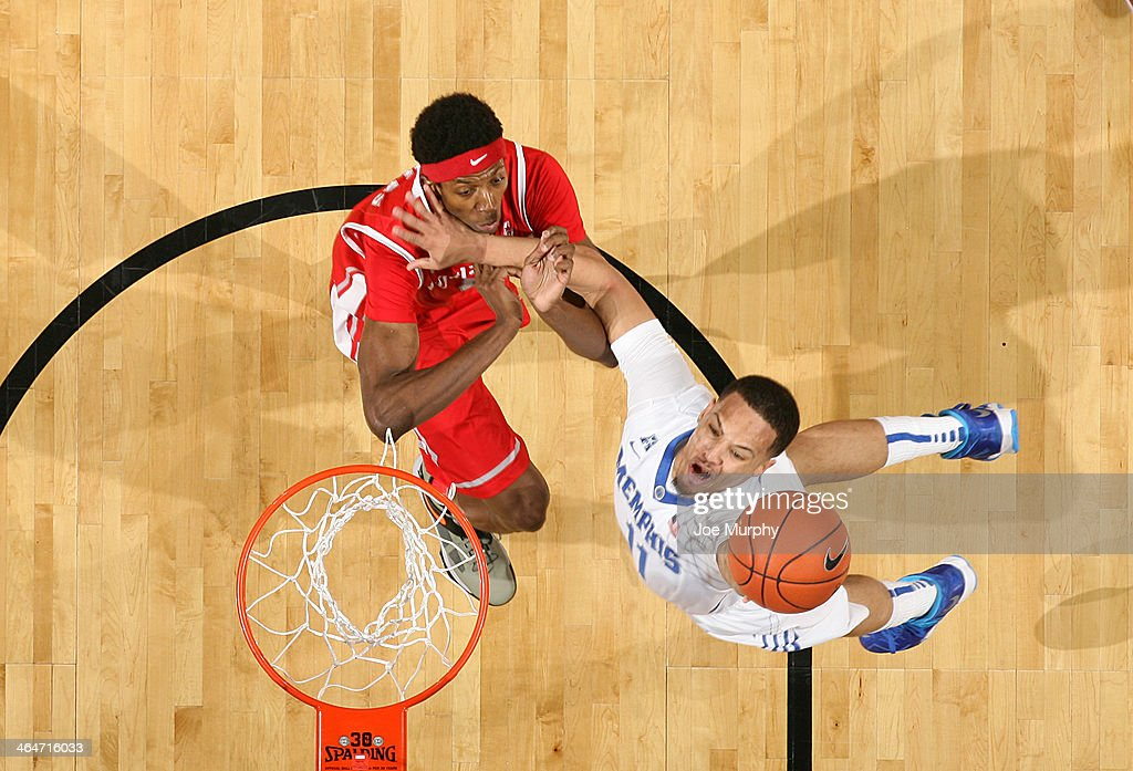 Michael Dixon Jr. #11 of the Memphis Tigers drives to the basket for a layup against Danrad Knowles #0 of the Houston Cougars on January 23, 2014 at FedExForum in Memphis, Tennessee. Memphis beat Houston 82-59.