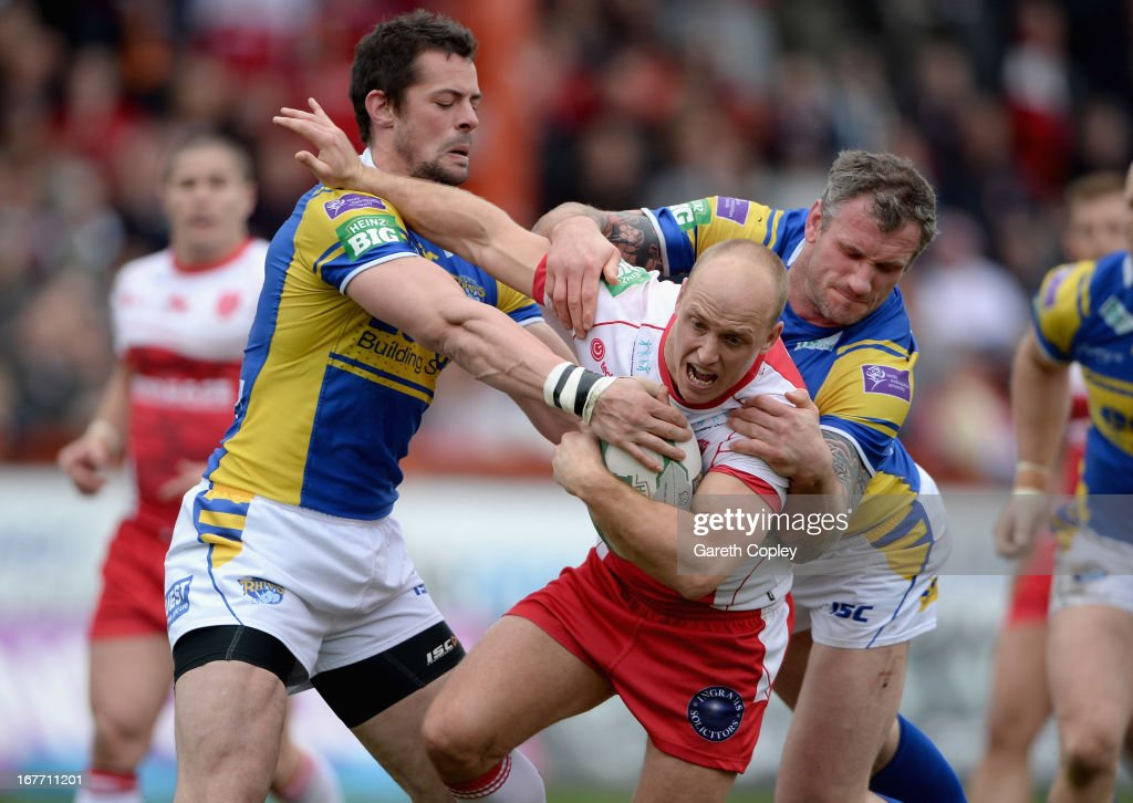 Michael Dobson of Hull KR is tackled by Ian Kirke and Jamie Peacock of Leeds during the Super League match between Hull Kingston Rovers and Leeds Rhinos at Craven Park Stadium on April 28, 2013 in Hull, England.