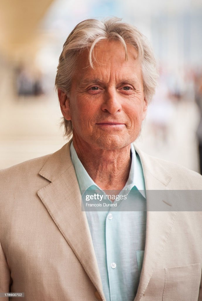 Michael Douglas poses next to the beach closet dedicated to him during a photocall on the Promenade des Planches for the movie 'Behind the...
