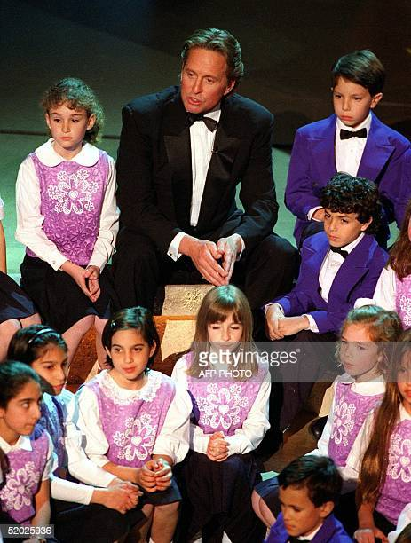 Michael Douglas sits with the Stephen S Wise Elementary School Choir to discuss his favorite childhood book entitled 'The Broken Mirror' during...