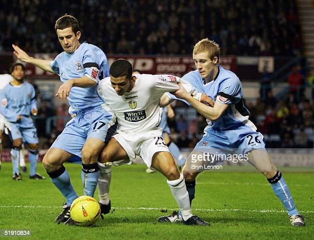 Michael Doyle and Stuart Giddings of Coventry City hold back Aaron Lennon of Leeds United during the CocaCola Football League Championship match...