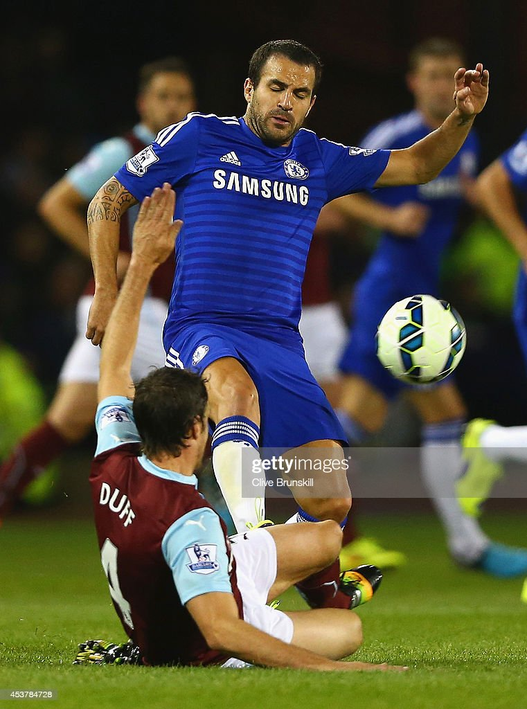Michael Duff of Burnley tackles Cesc Fabregas of Chelsea during the Barclays Premier League match between Burnley and Chelsea at Turf Moor on August 18, 2014 in Burnley, England.