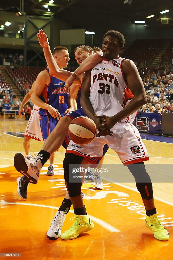 Michael Dunigan of Perth is fouled by Anthony Petrie of Adelaide during the round ten NBL match between the Adelaide 36ers and the Perth Wildcats at Adelaide Arena on December 9, 2012 in Adelaide, Australia.
